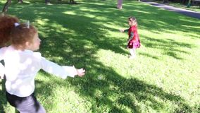Two happy girls jump among soap bubbles. In green summer park stock video footage
