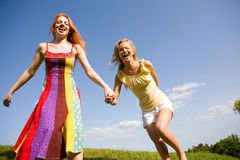Two happy girls jumping. Blue sky Stock Image