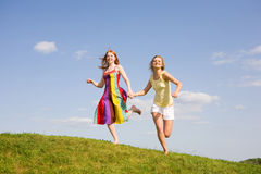 Two happy girls jumping. Blue Sky Stock Images