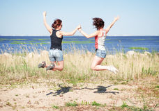 Two happy girls jumping on the beach Royalty Free Stock Images