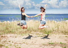 Two happy girls jumping on the beach in summer Royalty Free Stock Photography