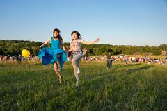 Two happy girls jumping high in blue sky on summer Stock Images