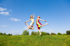 Two happy girls jumping together on green meadow. Against the backdrop of blue sky Royalty Free Stock Images
