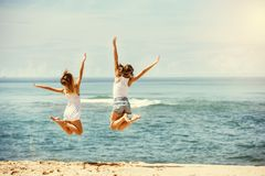 Two happy girls jumps at sunny beach. Travel concept with two happy girls jumping at hot sunny beach Stock Photo