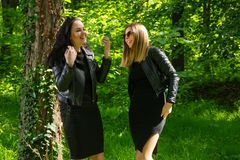 Two happy girls laugh with teeth smile on spring sunny day in the forest. Girls wear a black dress and leather jacket. Fashionable cute female posing in nature royalty free stock photography