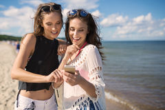 Two happy girls looking at phone on beach. Front portrait of two happy girls looking at phone on beach Stock Photo