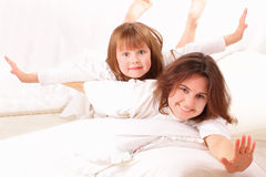 Two happy girls lying in bed Royalty Free Stock Photography
