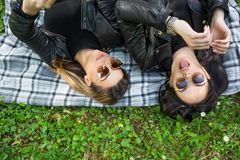 Two happy girls lying down on blanket in a green meadow on a spring day in nature. Girls wear sunglasses and a black jacket. One girl loll out tongue. Enjoying royalty free stock photo