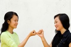 Two happy girls make peace to each other. Portrait of two asian female teenager make peace to each other after the fights. bury the hatchet Stock Image