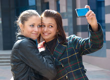 Two happy girls make self-portrait. On a street Stock Image
