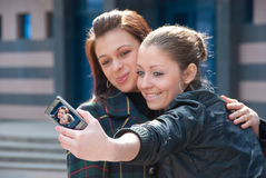 Two happy girls make self-portrait. On a street Stock Photo