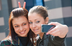 Two happy girls make self-portrait. On a street Stock Images