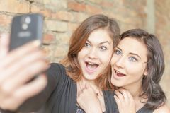 Two happy girls make selfie on mobile phone Royalty Free Stock Photography