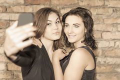 Two happy girls make selfie on mobile phone Royalty Free Stock Images
