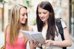 Two happy girls with map Stock Images