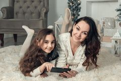 Two happy girls, mother and daughter lie on a floor in Christmas decorated room, use a mobile phone for access to Internet Royalty Free Stock Images