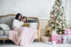 Two happy girls, mother and daughter siting on a sofa in Christmas decorated room. Royalty Free Stock Photos