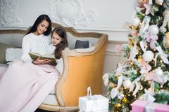 Two happy girls, mother and daughter siting on a sofa in Christmas decorated room. Royalty Free Stock Images