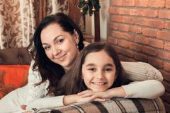 Two happy girls, mother and daughter siting on a sofa in Christm Royalty Free Stock Photo