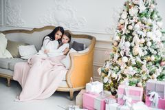 Two happy girls, mother and daughter siting on a sofa in Christmas decorated room. Stock Image