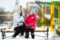 Two happy girls, mother and daughter sitting on a bench on a  pl Royalty Free Stock Photography
