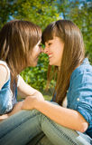 Two happy girls noses kiss. Outdoors Stock Photo
