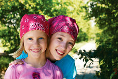 Two happy girls outdoors in kerchiefs on their heads Royalty Free Stock Image