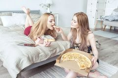 Two happy girls in pajamas spending time together at bachelorette party and eating pizza in bed. Stock Photos