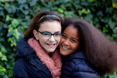 Two happy girls in the park. With coats Royalty Free Stock Photos