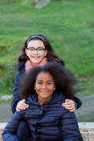 Two happy girls in the park. With coats Stock Photography
