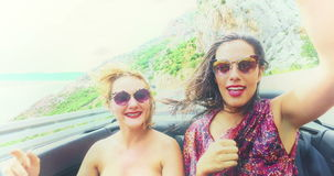 Two happy girls partying while riding in cabriolet, graded with yellow filter stock video footage