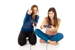 Two happy girls play video games. Two girls are playing video games Royalty Free Stock Photo