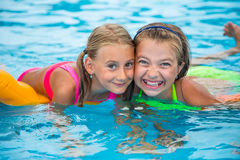 Two happy girls playing in the pool on a sunny day. Cute little girls enjoying holiday vacation.  Royalty Free Stock Photography