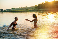 Two happy girls playing in river splashig water at Stock Photo