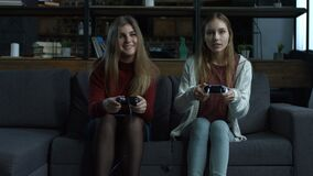 Two happy girls playing video games in a console stock footage