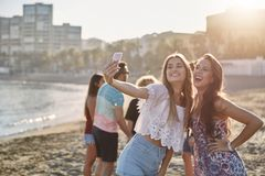 Two happy girls posing to selfie on beach. Portrait of two happy girls posing to selfie on beach Stock Photo