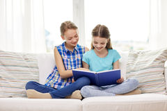 Two happy girls reading book at home Stock Photos