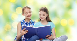 Two happy girls reading book over green background. People, children, friends, literature and friendship concept - two happy girls sitting and reading book over Stock Photo