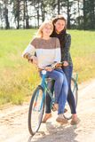 Two happy girls ride bicycles on countryside Stock Image