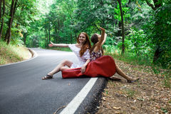 Two happy girls in a road hitchhiking with guitar case Royalty Free Stock Photo