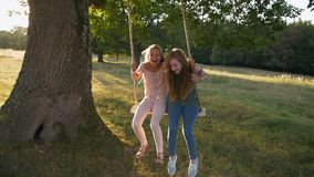 Two happy girls on rope swing - slow mo stock video footage