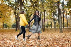Two happy girls running in autumn city park royalty free stock photo