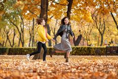 Two happy girls running in autumn city park royalty free stock images