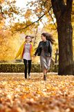 Two happy girls running in autumn city park royalty free stock image