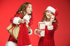 Two happy girls in santa claus hats with gift boxes Royalty Free Stock Photos