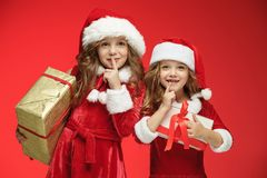 Two happy girls in santa claus hats with gift boxes Stock Images