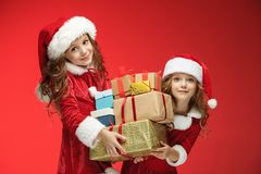 Two happy girls in santa claus hats with gift boxes Stock Photos