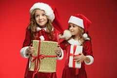 Two happy girls in santa claus hats with gift boxes at studio Royalty Free Stock Image