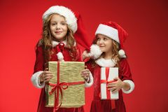Two happy girls in santa claus hats with gift boxes at studio Royalty Free Stock Images