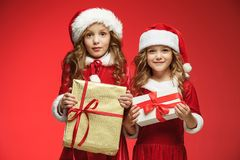 Two happy girls in santa claus hats with gift boxes at studio Royalty Free Stock Photography